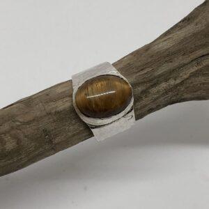 Sterlingsilverring med gedigen silverinfattad oval cabochon slipad tigeröga sten. Ringen har hamrat band