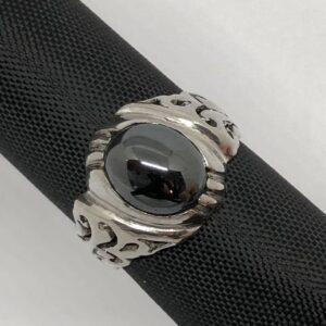 Sterlingsilverring med gedigen silverinfattad oval cabochon slipad hematit sten. Bandet har dekorativt genombrutet mönster.