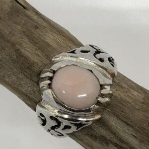 Sterlingsilverring med gedigen silverinfattad oval cabochon slipad rosa opal sten. Bandet har dekorativt genombrutet mönster.